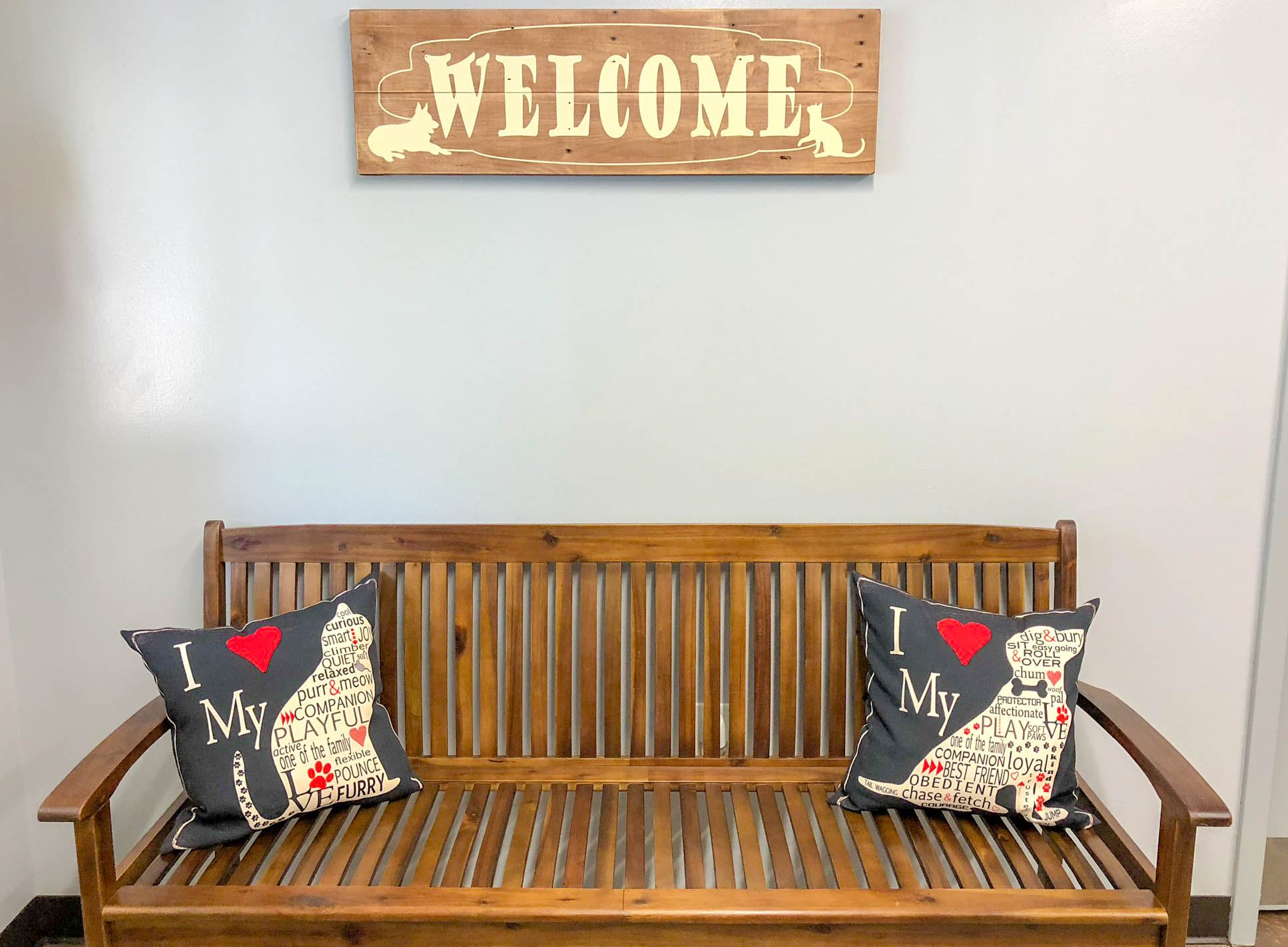 Animal Services Lobby bench with animal-themed pillows under a rustic welcome sign